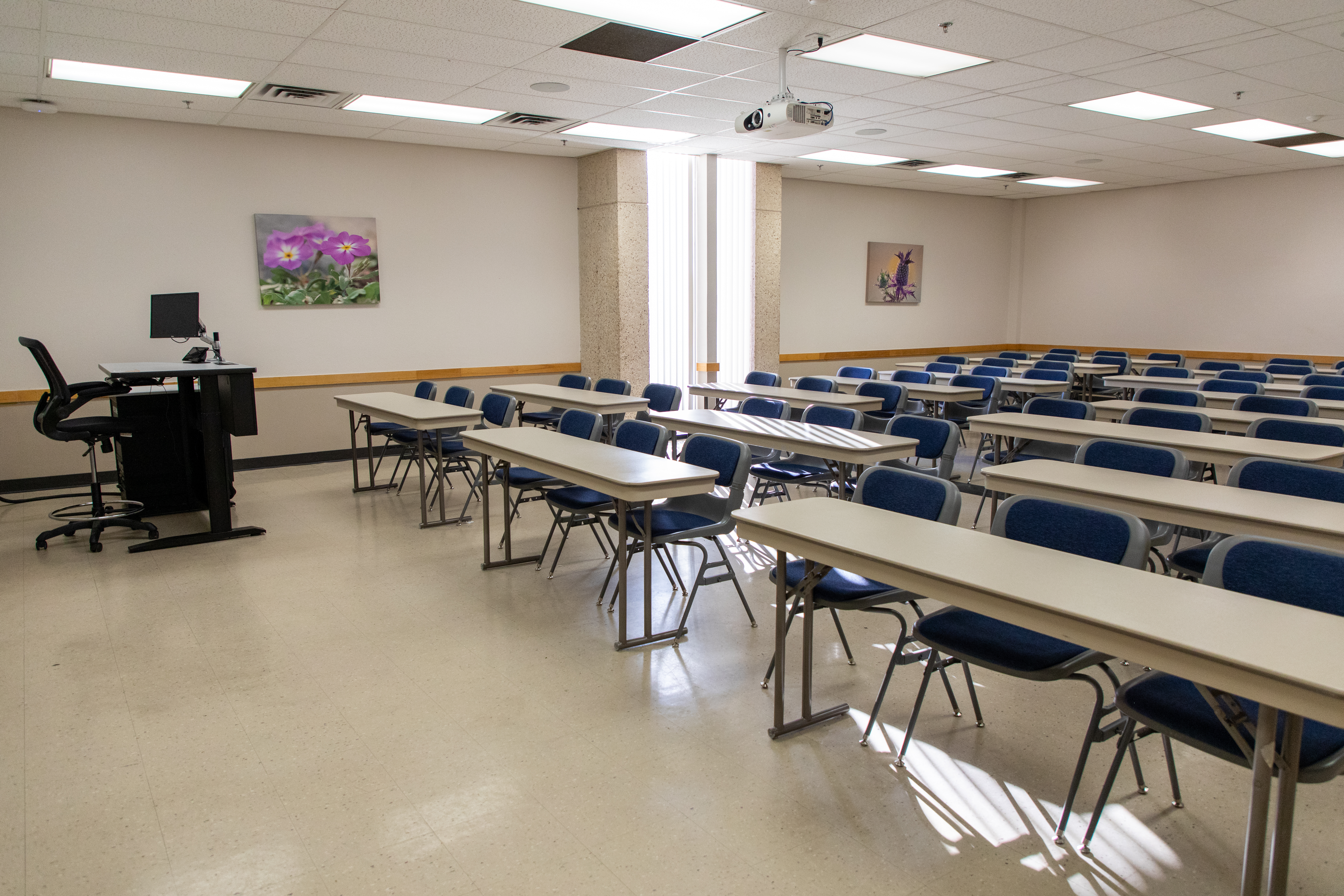 Large classroom with tables and chair facing forward.
