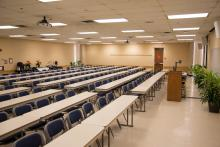 Large room with rows of tables and chairs facing a podium.